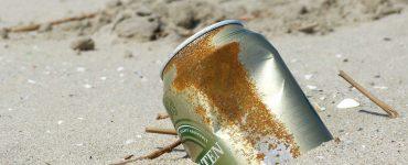 Lata de refresco abandonada en una playa.